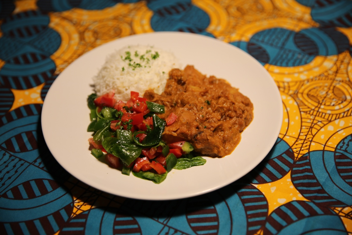 Lamb mafe peanut stew with soft rice and fresh salad on yellow and blue table cloth