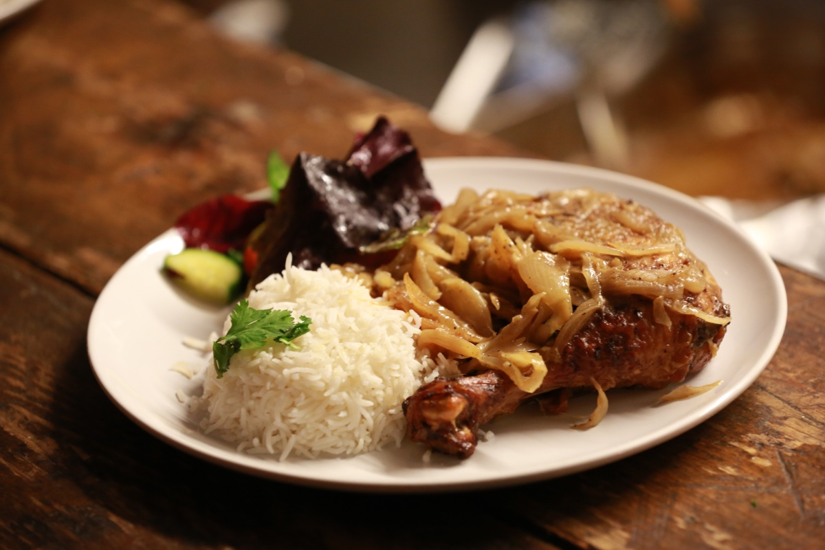 Yassa chicken = Spicy marinated chicken with onion sauce, olives and rice - Little Baobab - London